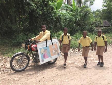 Kinder begleiten Motoradfahrer mit Schulmaterial